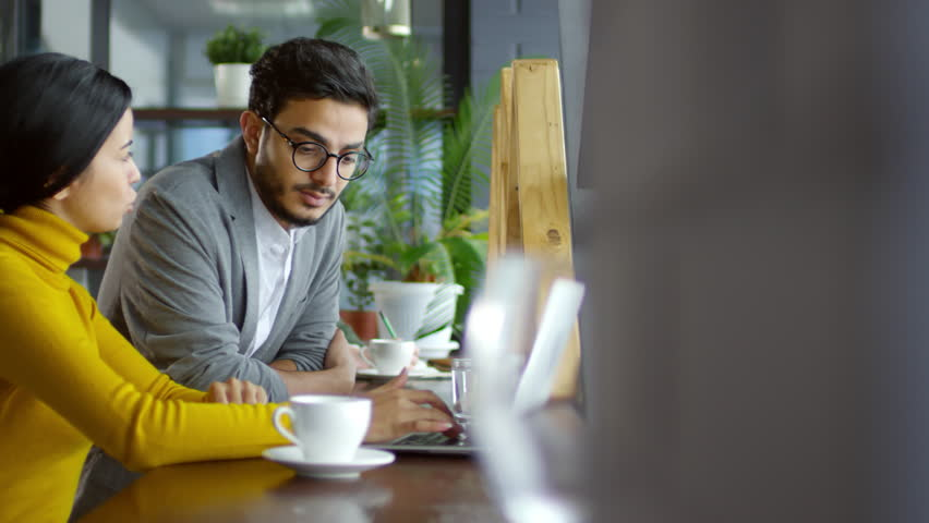 Middle eastern businessman speaking with female Asian colleague while sitting together at cafe table beside the window and working on laptop | Shutterstock HD Video #1025911700
