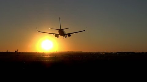 4K. Commercial airplane is landing on the airport runway during sunset. The sky is orange. Silhouette of an airplane that is landing.
