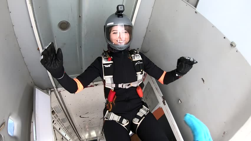 Skydiving. Young woman is jumping out of a plane. Slow motion. | Shutterstock HD Video #1025921408