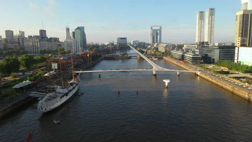 Aerial drone view of Puerto Madero harbor with Puente de la Mujer bridge and skyscraper buildings in the background. Buenos Aires, Argentina. | Shutterstock HD Video #1025954024