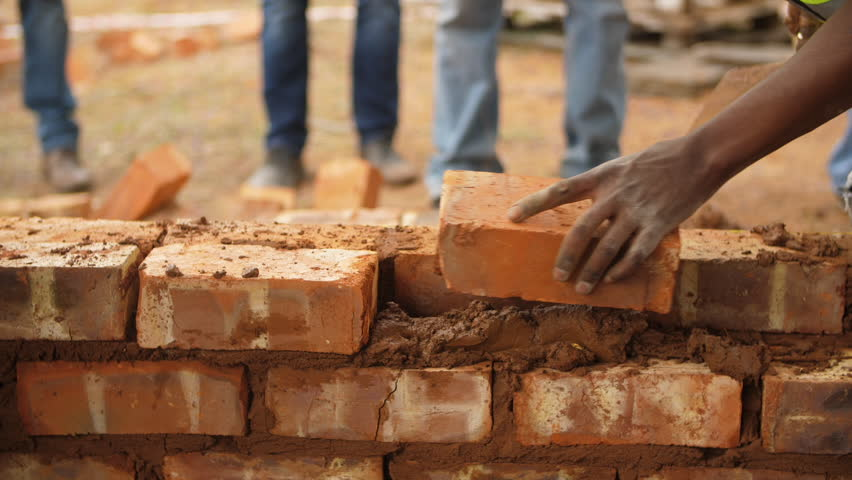 Black male volunteer worker lays brick into wall with cement using trowel | Shutterstock HD Video #1025960810
