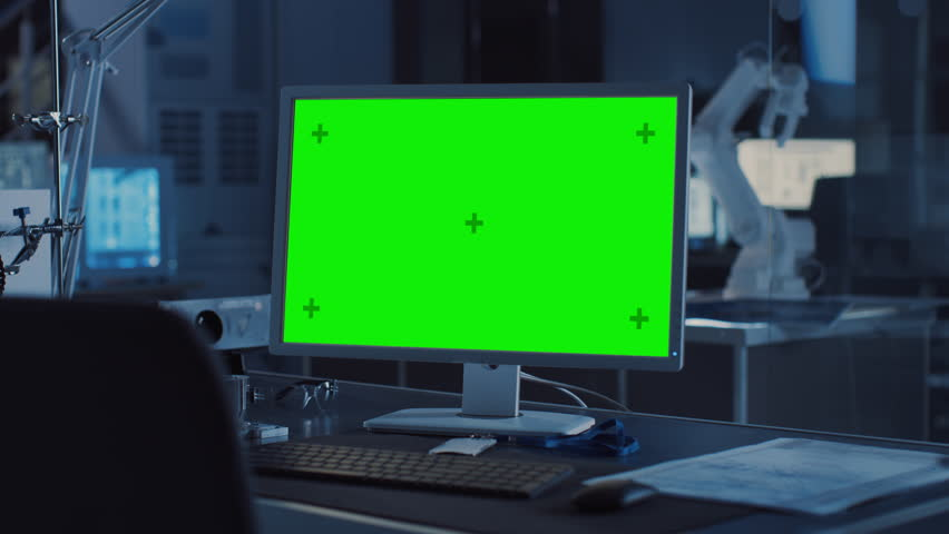 On the Desk Computer with Isolated Green Mock-up Screen Display. In the Background Robot Arm Concept Standing in Heavy the Dark.Industry Engineering Facility. Shot on 8K RED Camera #1025971127