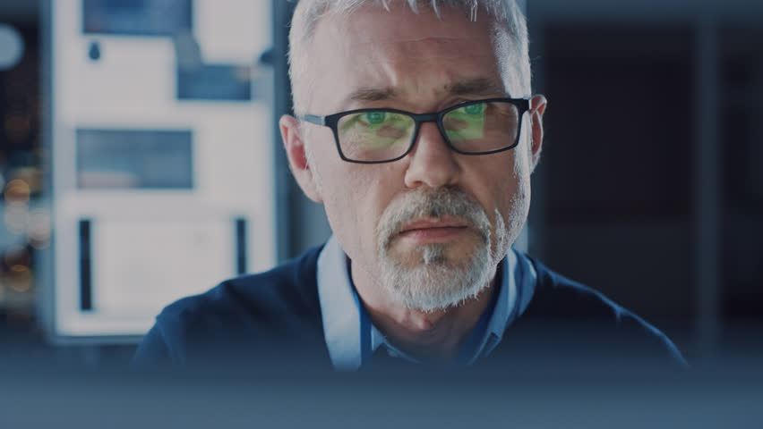 Portrait of Handsome Middle Aged Engineer Wearing Glasses Works on Personal Computer. In the Background High Tech Engineering Facility. Shot on 8K RED Camera. #1025971223