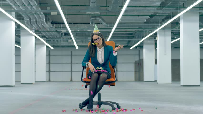 Office employee throws confetti and blows a festive whistle, sitting in a chair. Royalty-Free Stock Footage #1025978543