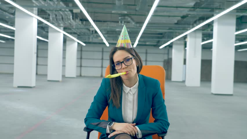 One office worker in a birthday cap blows a whistle, sitting in a chair. Royalty-Free Stock Footage #1025978555