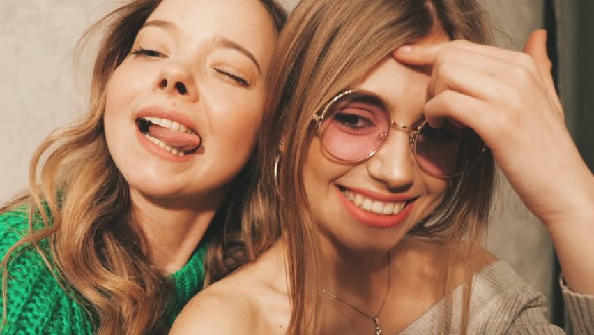 Two beautiful smiling girls in round sunglasses.Women in summer hipster clothes taking selfie pictures on  camera. Models making funny faces and having fun, Slow motion | Shutterstock HD Video #1025992166
