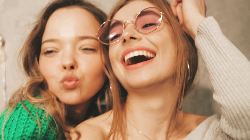 Two beautiful smiling girls in round sunglasses.Women in summer hipster clothes taking selfie pictures on  camera. Models making funny faces and having fun, Slow motion | Shutterstock HD Video #1025992172