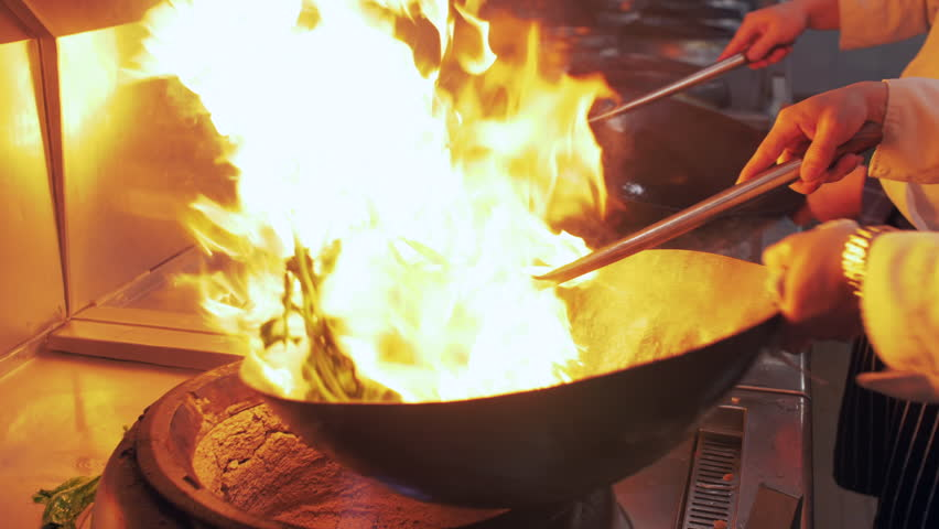 Slow motion of Chef Cooking in the Kitchen, Restaurant wok fire cooking Close up, cook frying vegetable in the commercial kitchen. Chinese style Sichuan food cooking 4k clip