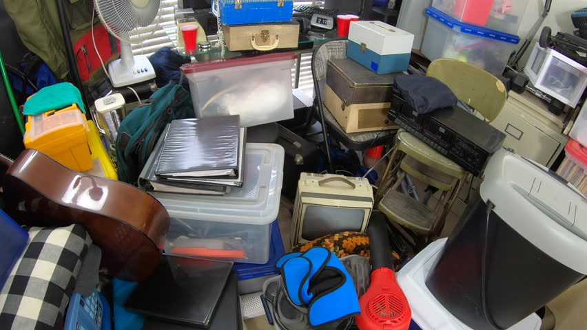 Cluttered object filled room.  Slow dolly out over piles of household items, vintage electronics, business equipment and miscellaneous junk.   Shutterstock HD Video #1025996816