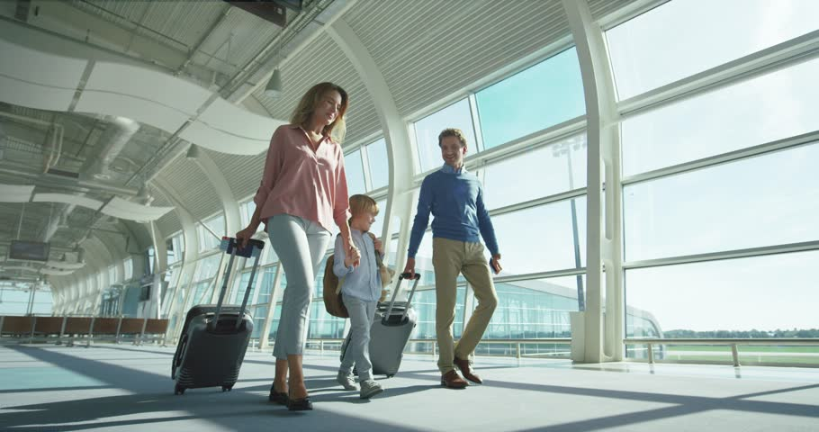 Caucasian parents with small nice son and big suitcases on wheels passing through the camera in the airport passage while going to the departure or arrival gates.