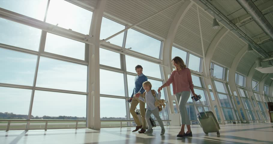 Little nice with backpack walking the airport hall with his parents with suitcases on wheels while family flying on vacations. Royalty-Free Stock Footage #1026000341