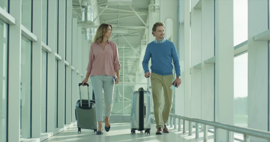 Happy Caucasian just-married couple walking by the arrival passage to the gates in the airport after landing while having honey moon. | Shutterstock HD Video #1026000389