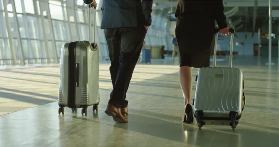 Back view on the Caucasian businessman and businesswoman walking the airport hall and carrying their suitcases on the wheels before the departure to the working trip. Rear. Camera moving from feet up.   Shutterstock HD Video #1026000554