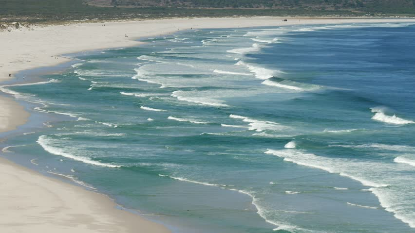 Side high angle view of blue ocean waves breaking on curved shoreline to large sandy beach, unpolluted, clean ocean Nordhoek, Cape, South Africa | Shutterstock HD Video #1026002825
