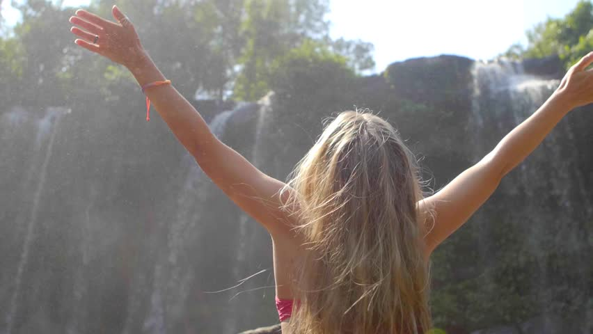 Rear view of young woman sitting in front of waterfall with her hands raised. Female tourist with her arms outstretched. Freedom, success,happiness and vacation concept. | Shutterstock HD Video #1026014444