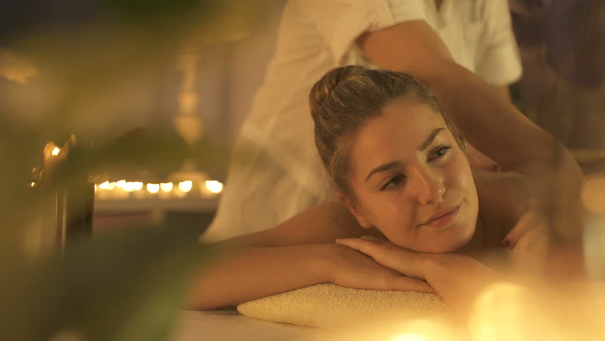 Woman enjoying body massage at spa club.
