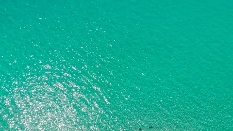 Aerial view of blue sea surface with light reflections. Top view of transparent turquoise ocean water surface.