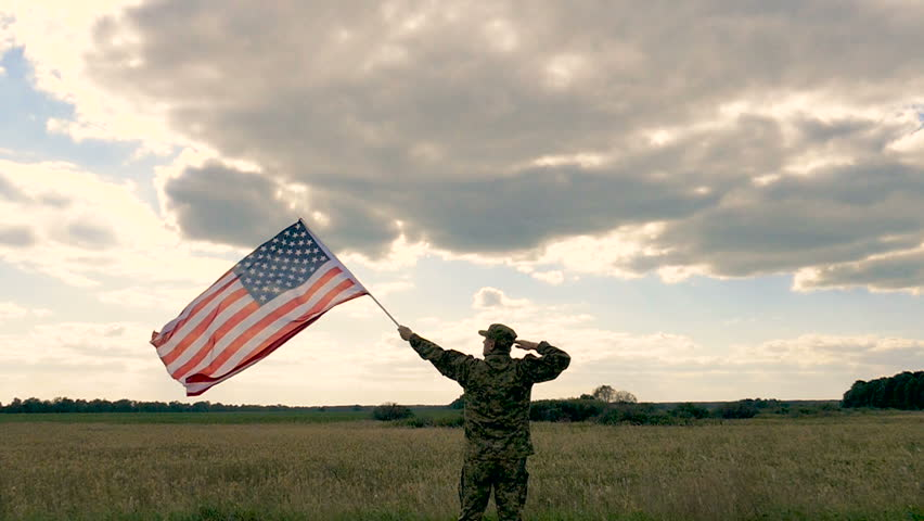 Soldier salute with  American flag against blue sky. Outdoor slow motion scene #1026025232