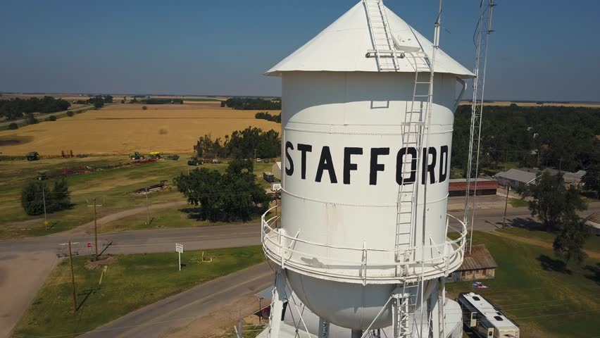 Aerial pullback from Stafford water tower to reveal small farming city, Kansas, USA