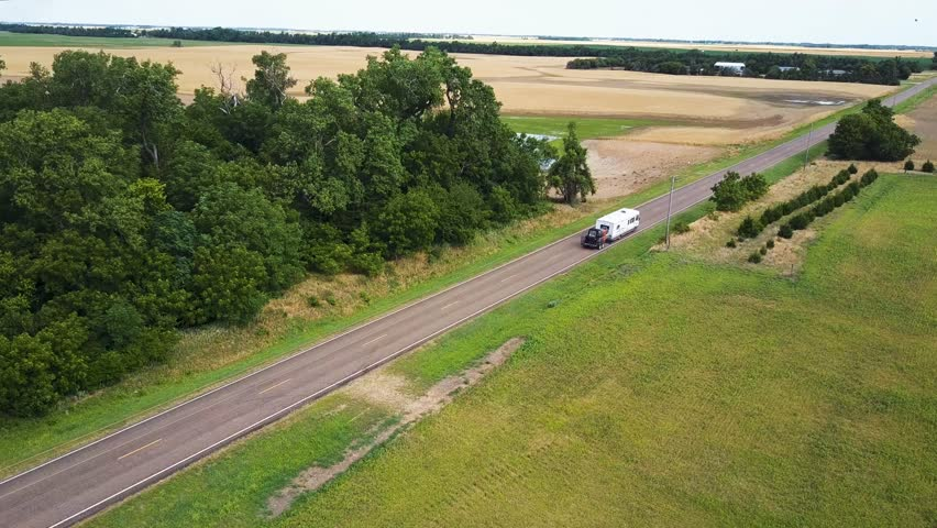 RV travels down empty country road in rural Kansas, Aerial tracking shot 4k