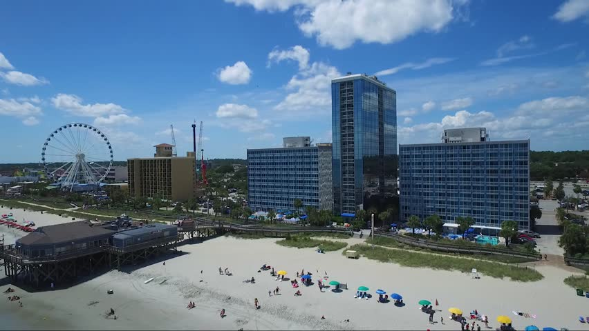 Drone flying near ocean front resorts, pier and sky wheel in Myrtle Beach SC