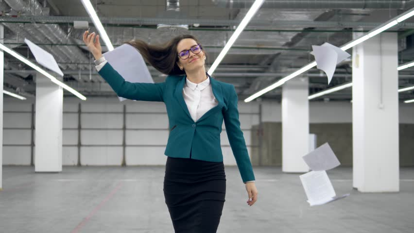 Happy office worker starts to dance and throws away documents.