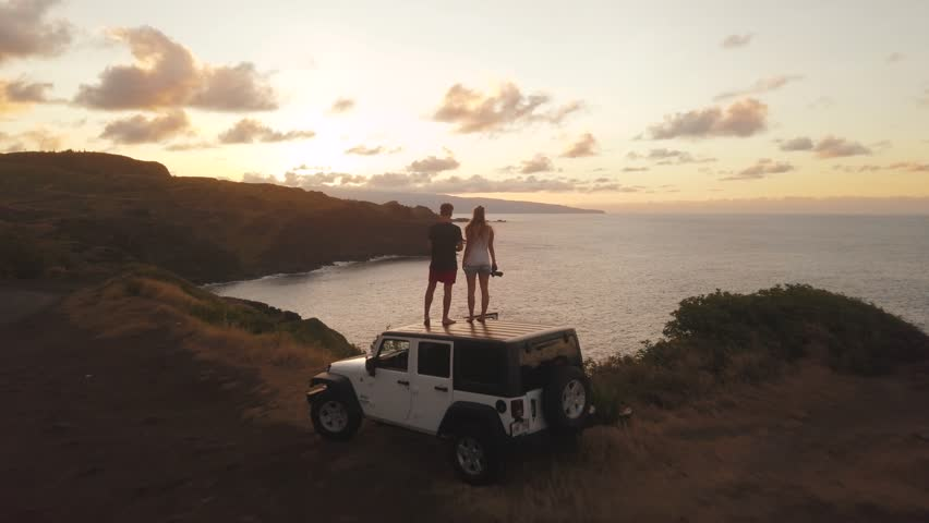 Drone panning over islands and the ocean in Hawaii zooming out on a couple of people standing on their car during a beautiful orange hazy sunrise with low cloud and bright skies