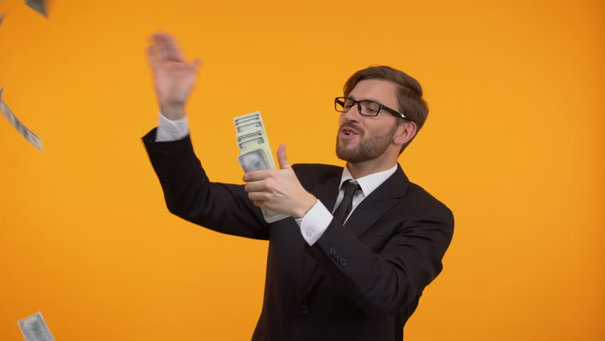 Positive businessman throwing dollar banknotes in air, spending money, success