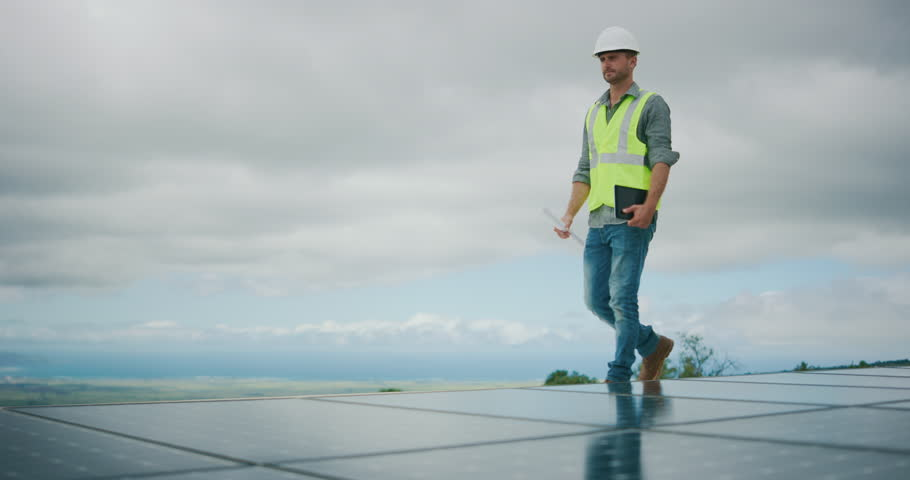 Sustainable green energy jobs, solar panel technician surveying solar panels #1026077900