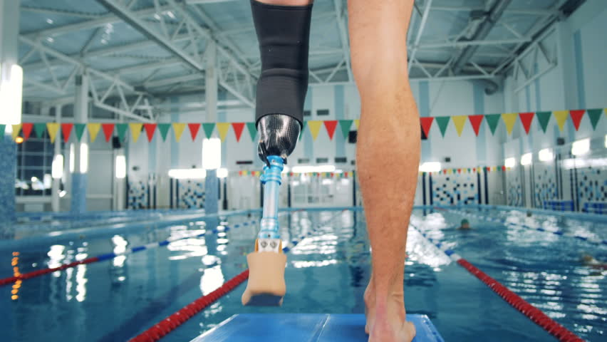 Swimmer with a leg prosthesis training near a pool, bionic equipment.