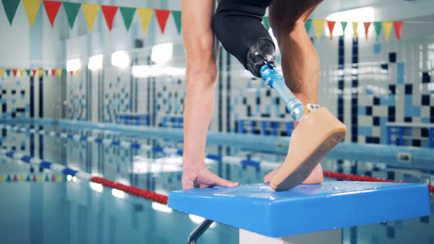 A man with bionic leg jumps into a pool, swimming workout.