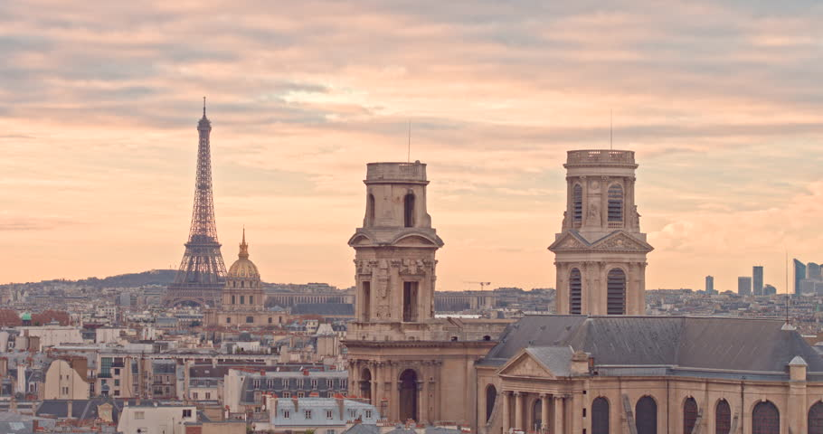 City of Paris France at Sunset with aerial view by drone on saint sulpice cathedral and Eiffel Tower, with full city cityscape and dawn colors