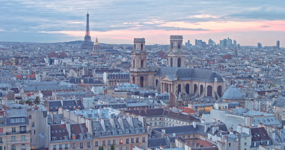 Paris cityscape aerial drone shot at Dawn with Eiffel Tower and Cathedral view. Colorful sky, clouds and rooftops for a beautiful parisian landscape