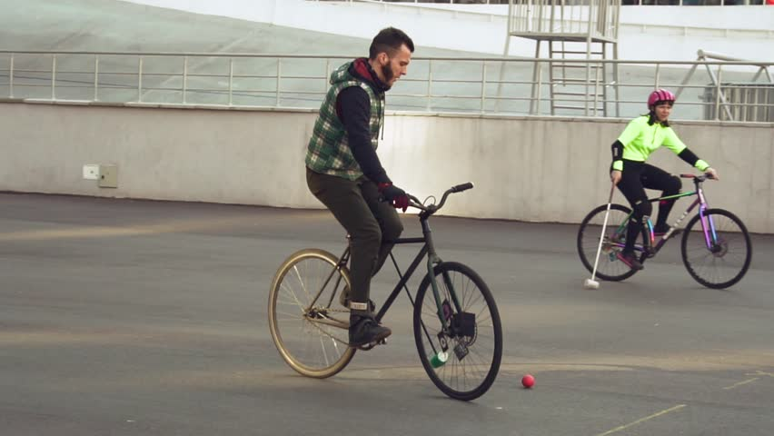 March 17, 2019. Ukraine, Kiev. Bike polo game. group of people team on city bikes are training playing team game in stadium. man on bicycle with stick in his hands kicks ball into the goal. | Shutterstock HD Video #1026113360