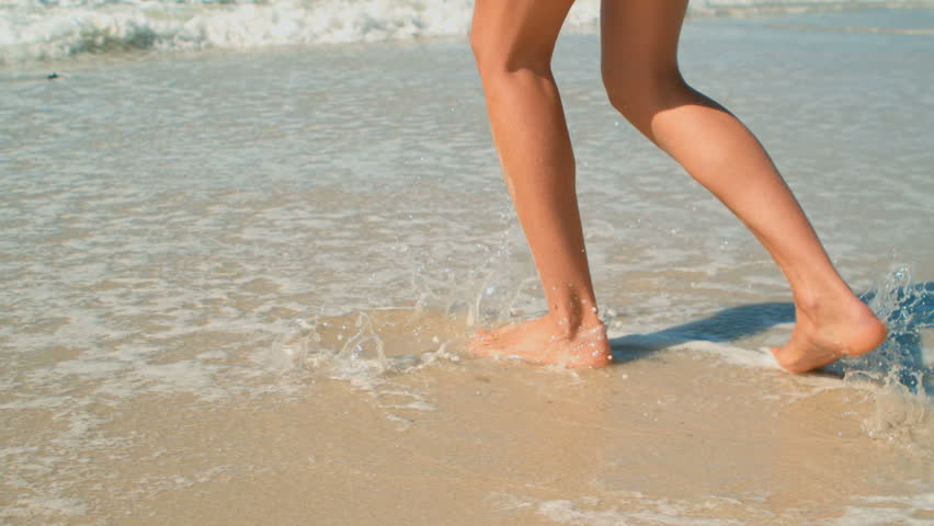 Low section of Caucasian woman playing in waves on beach in the sunshine. She is kicking waves  | Shutterstock HD Video #1026119663