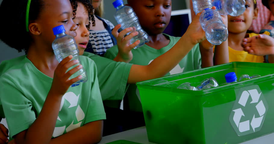 Front view of group of diverse schoolkids putting bottles in recycle container at desk in classroom. They are studying about green energy and recycle.