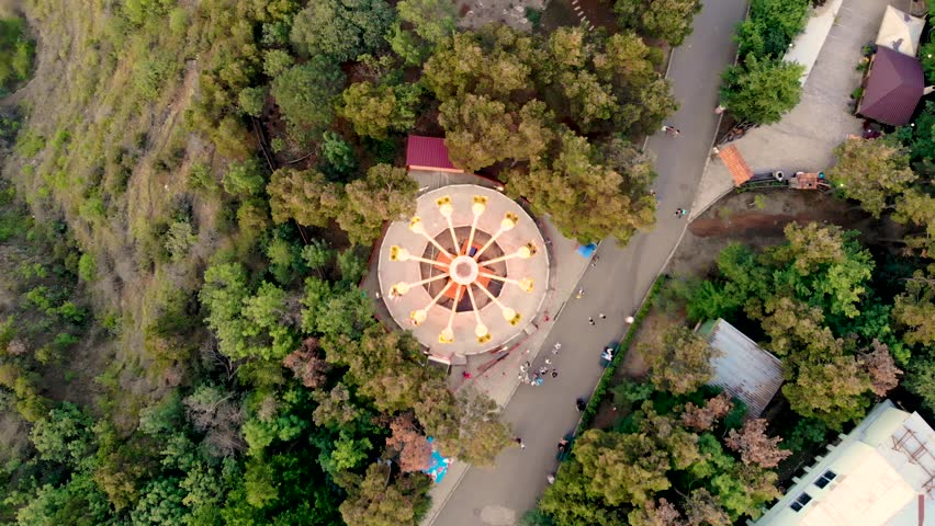 Hypnotic aerial view of spinning carousel in amusement park in Tbilisi, Georgia. People riding the chairoplane carousel and having fun at the funfair. Taken by drone. Royalty-Free Stock Footage #1026123773