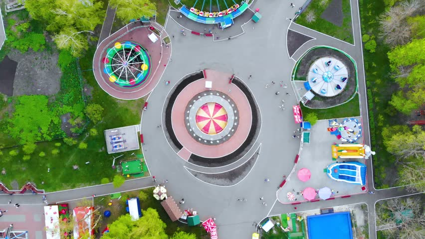 Hypnotic aerial view of spinning carousel in amusement park. People riding the chairoplane carousel and having fun at the funfair. Taken by drone. Royalty-Free Stock Footage #1026123776