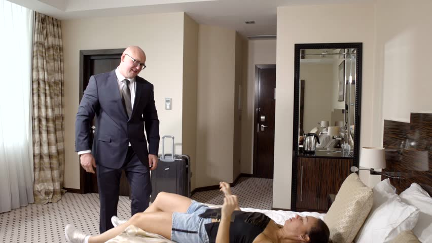 adult bald man and female prostitute are caressing in hotel room, man is taking off his jacket