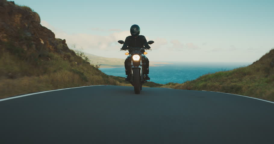 Motorcyclist riding fast on country road with ocean in the background, motorcycle adventure lifestyle | Shutterstock HD Video #1026135182