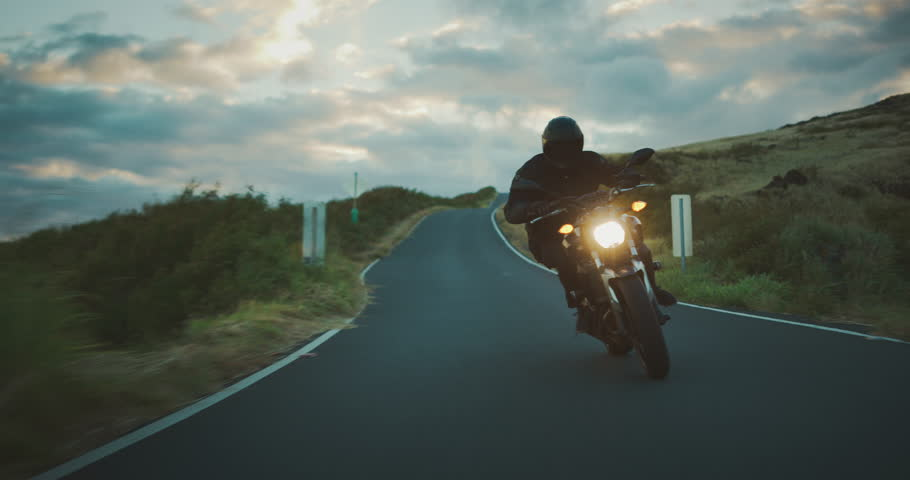 Motorcyclist riding fast at dusk on country road in slow motion, motorcycle adventure lifestyle | Shutterstock HD Video #1026135362