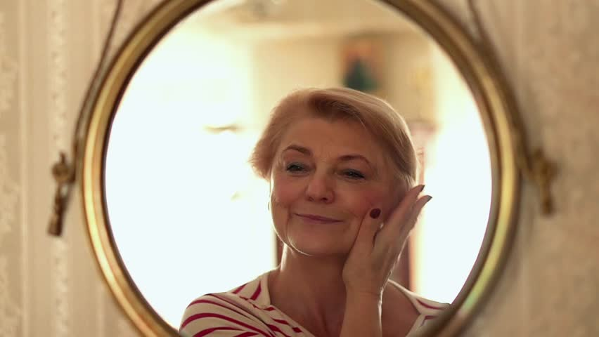 Senior, happy woman checking her look in front of the mirror, slow motion  Royalty-Free Stock Footage #1026150836