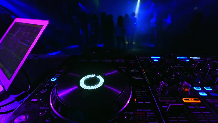 Music controller DJ mixer in a nightclub at a party on the background of a dancing crowd of people | Shutterstock HD Video #1026157724
