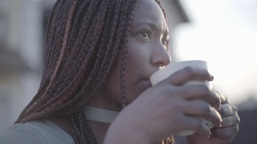 Close up portrait of confident african american young black smiling woman with hot cup of coffee on the street. Slow motion | Shutterstock HD Video #1026158876