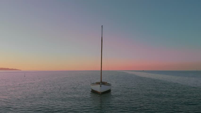 Lone sailboat moored in tranquil baywaters - magic hour. 4K drone - angle shift 30seconds in to give two options.