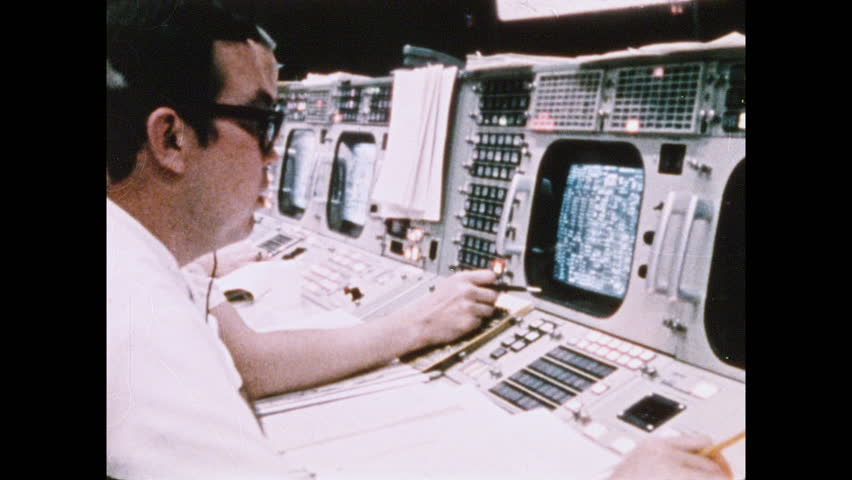 1960s: Men in front of monitor in NASA mission control room. Men in mission control. Hand writing in book. People sitting at monitors. People looking over data on paper.