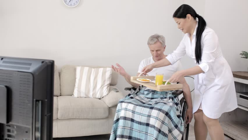 Carrying Nurse In White Coat Bring Breakfast To Disabled Person And Places It On His Knees As He Sits In A Wheel Chair. Smiling Senior Man In An Armchair Places The Breakfast On His Knees Inviting The | Shutterstock HD Video #1026164015
