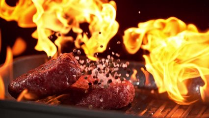 Super slowmotion footage of throwing fresh beef meat burger and pepper on ignited pan, 1000fps 4k