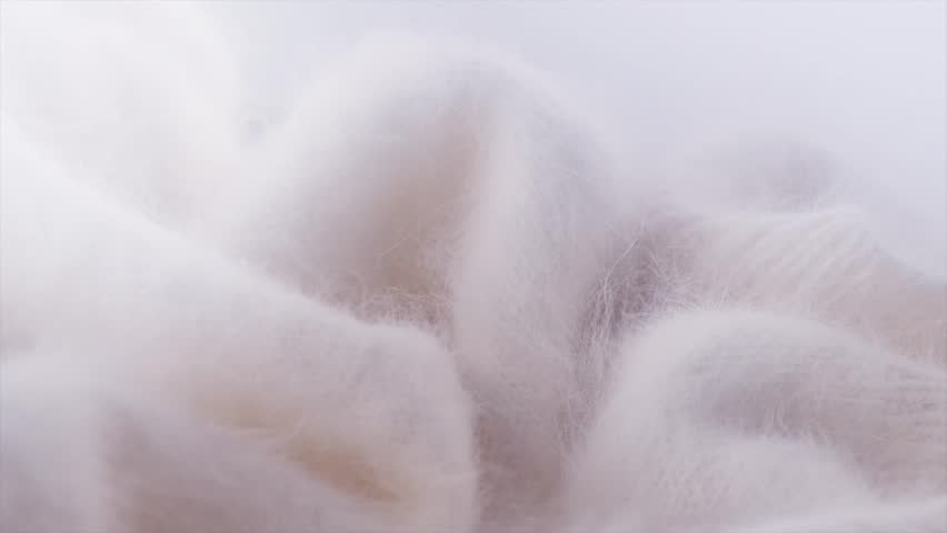 Soft Mohair Wool background. Alpaca wool mohair clothes texture closeup. Natural Cashmere Soft and fluffy merino wool macro shot. Woolen fabric. Knitted hairy detail texture Rotated. 4K UHD slowmo