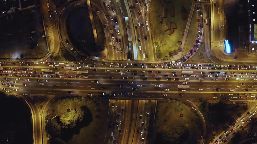 Aerial top view of cloverleaf  Interchange road at rush hour. Birds eye of city traffic at night time. City lights and cars stuck in Javier Prado and Via Expresa highways.   Shutterstock HD Video #1026179564